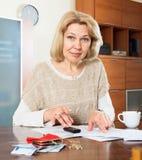 Allvarlig kvinnakvinna som arbetar med dokumentpengar Arkivfoto