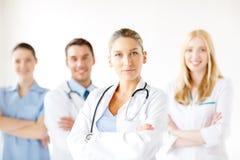 Allvarlig kvinnlig doktor framme av den medicinska gruppen royaltyfri fotografi