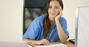 Allvarlig kvinnlig doktor på bärbar datordatoren arkivfoton