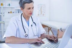 Allvarlig kvinnlig doktor som använder hennes bärbar datordator Arkivbild