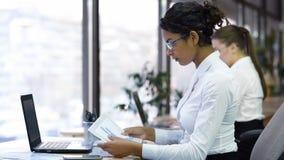 Allvarlig kvinnlig läsning för kontorschefen kartlägger och att kontrollera data som förbereder rapporten royaltyfri bild