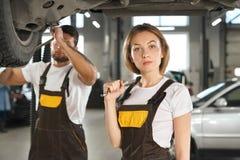 Allvarlig kvinnlig mekaniker som ser kameran och håller skiftnyckeln royaltyfri foto