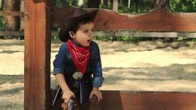 Allvarlig liten cowboy med leksakvapensammanträde arkivfilmer
