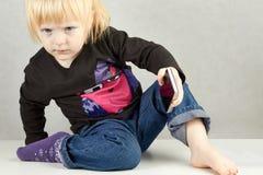 Allvarlig liten flicka med en telefon Royaltyfri Fotografi