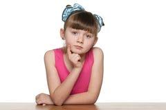 Allvarlig liten flicka på skrivbordet Arkivfoton