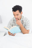 Allvarlig läsebok för ung man i säng Arkivfoton