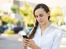 Allvarlig läsning för ung kvinna något på den smarta telefonen Royaltyfri Bild