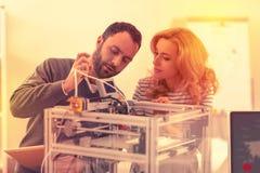 Allvarlig man och kvinna som grejar med mekanismen av en splitterny skrivare 3D arkivfoton