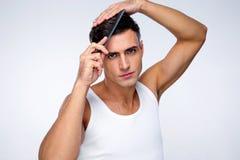 Allvarlig man som kammar hans hår Arkivfoto