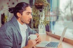 Allvarlig man som ser bärbara datorn, medan dricka hans kaffe eller te royaltyfri bild