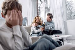 Allvarlig man som skakar hans alkoholiserade fru vid skuldrorna, medan tala Arkivfoton