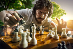 Allvarlig man som spelar schack arkivfoton