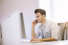 Allvarlig man som talar på mobiltelefonen, medan genom att använda bärbar datordatoren på skrivbordet i studie Royaltyfri Bild