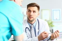 Allvarlig manlig doktor som frågar kollega för rådgivning om svårt medicinskt fall fotografering för bildbyråer