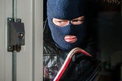Allvarlig maskerad hållande kofot för man, medan se in i husvind Royaltyfri Foto