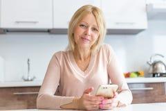 Allvarlig mellersta ålderaffärskvinna som använder en smartphone royaltyfri bild