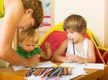Allvarlig moder och barn som drar med blyertspennor Arkivbilder