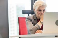 Allvarlig mogen affärskvinna som i regeringsställning använder bärbara datorn på skrivbordet royaltyfri fotografi