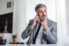 Allvarlig mogen affärsman med smartphonen som sitter på tabellen som gör en påringning royaltyfria bilder