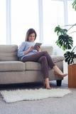 Allvarlig mogen kvinna som arbetar i bärbar dator, medan sitta på soffan royaltyfri fotografi