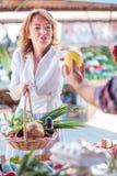 Allvarlig mogen kvinna som köper nya organiska grönsaker i en lokal marknadsplats arkivfoto