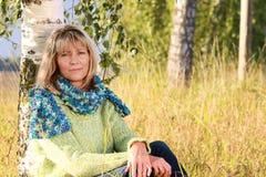 Allvarlig mogen kvinna som kopplar av i natur Arkivfoto
