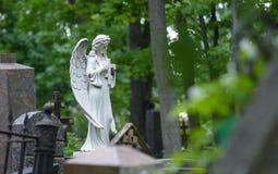 Allvarlig monument i kyrkogården, i sommaren som omges av gröna träd Royaltyfri Bild