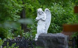 Allvarlig monument i kyrkogården, i sommaren som omges av gröna träd Royaltyfri Fotografi
