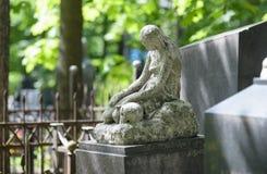 Allvarlig monument i kyrkogården, i sommaren som omges av gröna träd Arkivfoton