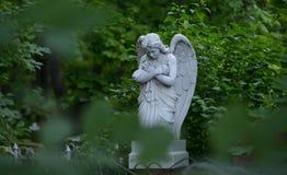 Allvarlig monument i kyrkogården, i sommaren som omges av gröna träd Arkivbilder
