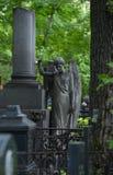 Allvarlig monument i kyrkogården, i sommaren som omges av gröna träd Royaltyfria Foton