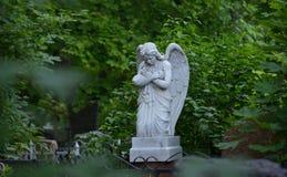Allvarlig monument i kyrkogården, i sommaren som omges av gröna träd Fotografering för Bildbyråer