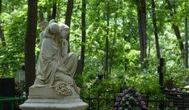 Allvarlig monument i kyrkogården, i sommaren som omges av gröna träd Royaltyfria Bilder