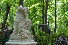 Allvarlig monument i kyrkogården, i sommaren som omges av gröna träd Arkivbild