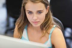 Allvarlig nätt student som arbetar på datoren Fotografering för Bildbyråer
