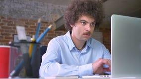 Allvarlig nerdy affärsman med mustaschen och lockigt hår som arbetar på bärbara datorn och tar anmärkningar som sitter i modernt  stock video
