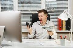 Allvarlig och fängslad affärsman i skjortasammanträde på skrivbordet som arbetar på datoren med den moderna bildskärmen Chef elle arkivbilder