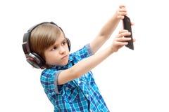 Allvarlig pojke i hörlurar med smartphonen royaltyfri fotografi