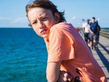 Allvarlig pojke på en pir på det baltiska havet arkivbilder