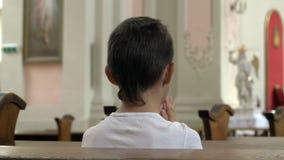 Allvarlig pojke som ber i kyrkan bara arkivbild