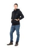 Allvarlig säker manlig modell i svart med huva omslag med händer i fack Arkivbild