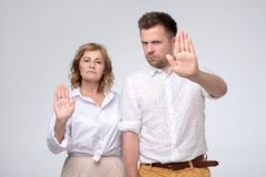 Allvarlig säker mogen man och kvinna som gör stoppgest med utsträckta armar arkivbilder