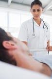 Allvarlig sjuksköterska som tar omsorg av en tålmodig Arkivfoto