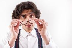 Allvarlig smart man som sätter på glasögon Royaltyfria Foton