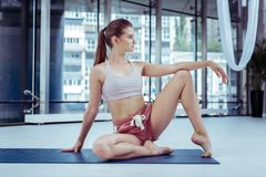 Allvarlig sportive kvinna som utbildar hennes akrobatiska expertis royaltyfri foto