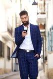 Allvarlig stilfull affärsman som går i stadsgata Arkivbilder
