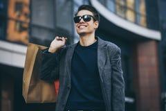 Allvarlig stilfull ung man med solglasögon som går i stads- gata och tycker om Black Friday shopping i moderiktig diversehandel i royaltyfri bild