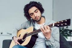 allvarlig stilig gitarrist som spelar den akustiska gitarren arkivfoton