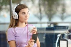 Allvarlig tonåring som lyssnar till musik i en stång Arkivbilder
