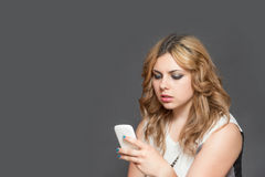 Allvarlig tonårs- flicka som ser koncentriskt hennes smarta telefon royaltyfri foto